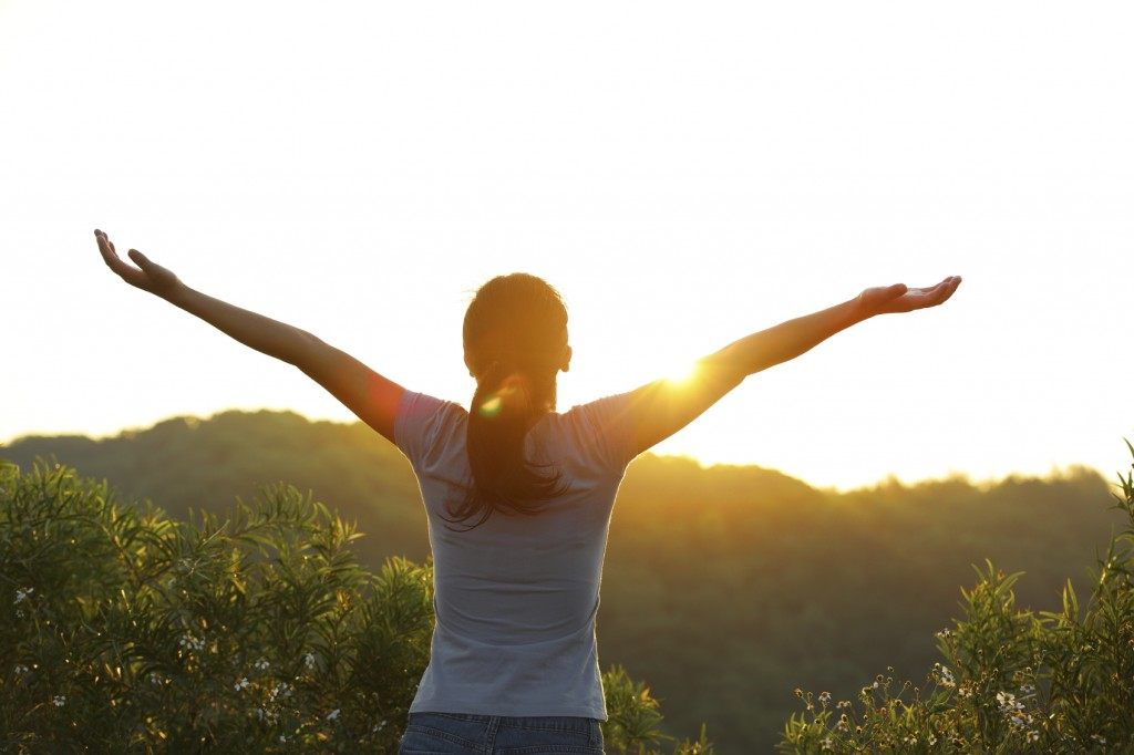 strong confident woman open arms to sunrise