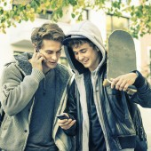 Young hipster brothers having fun with smartphone - Best friends