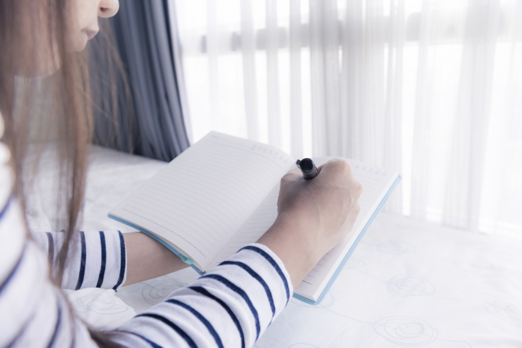 female hands holding pen and opened diary book