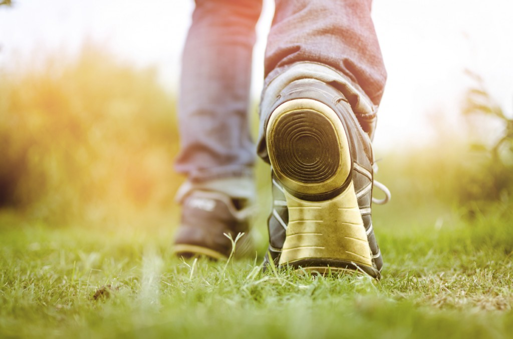 feet walking towards sunlight or going ahead towads sunrise or sunset on the grass or park or field running or morning walk or workout,