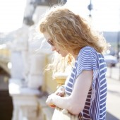 Woman with curly hair looking down on bridge