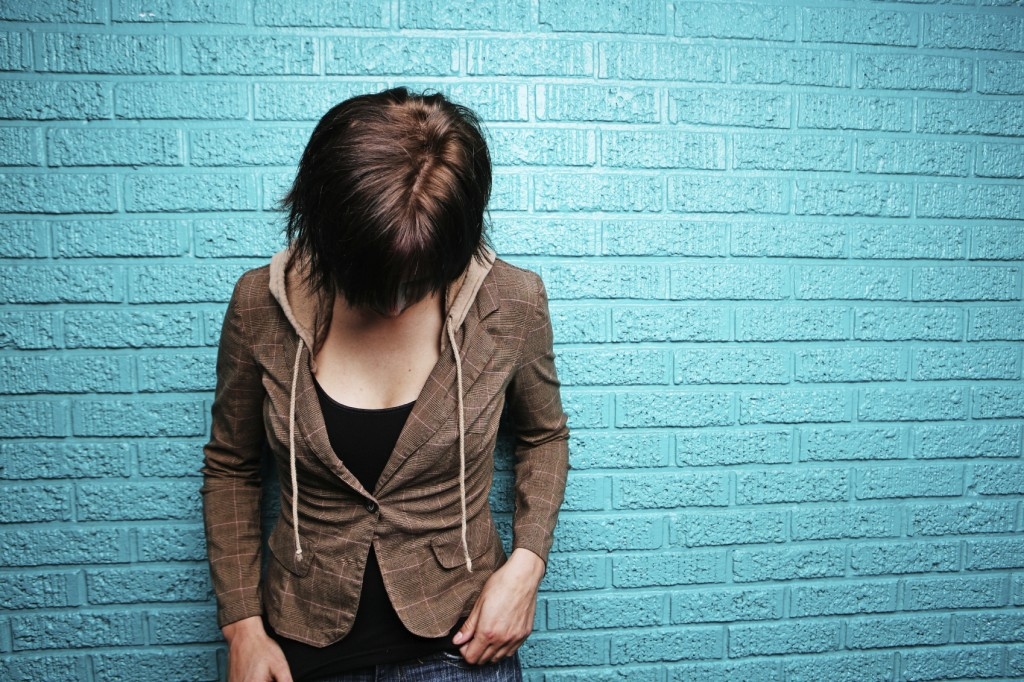 Shy Young Woman in Front of Bright Blue Wall