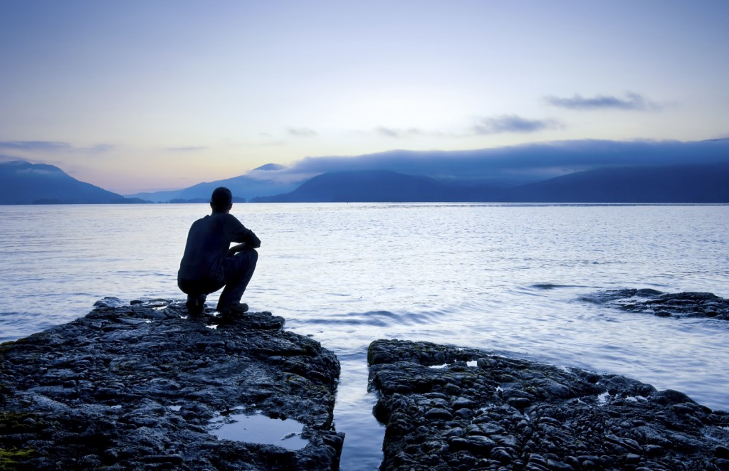 Man sitting on a small island watching the sunrise,
