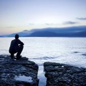 Man sitting on a small island watching the sunrise,