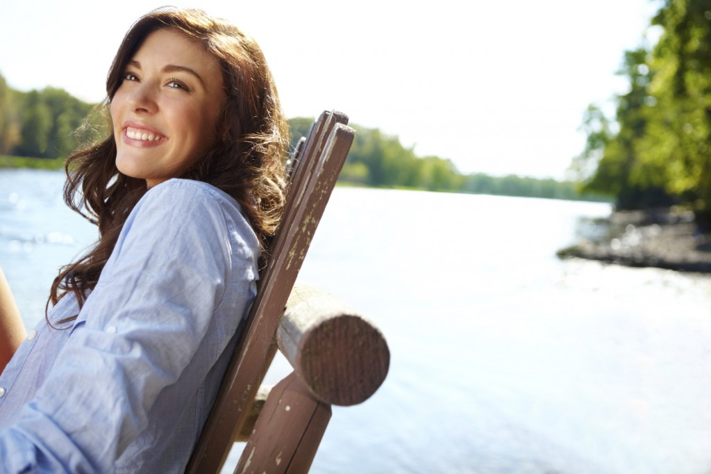 Gorgeous young woman sitting by a beautiful lake on a summer's day -