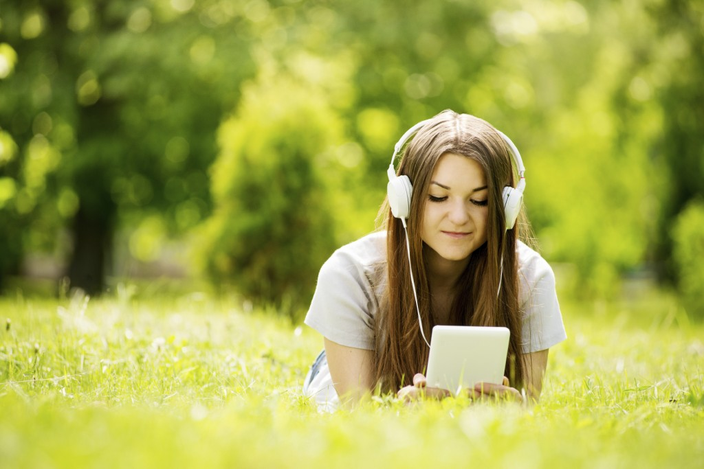 Young woman lying on the grass listening to music