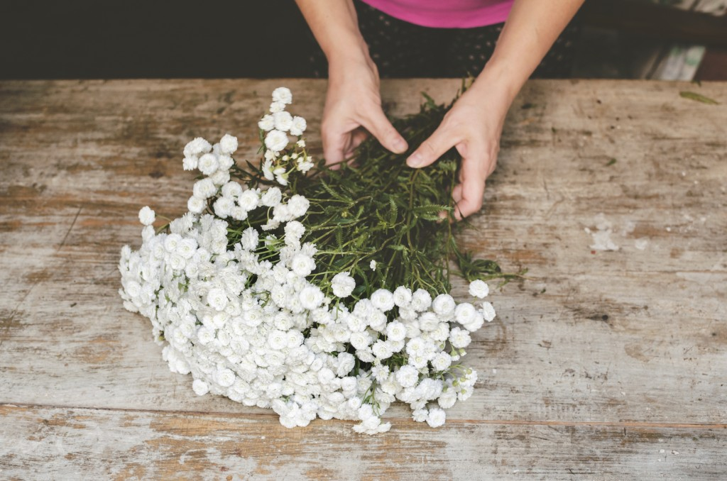 woman bundling white flowers