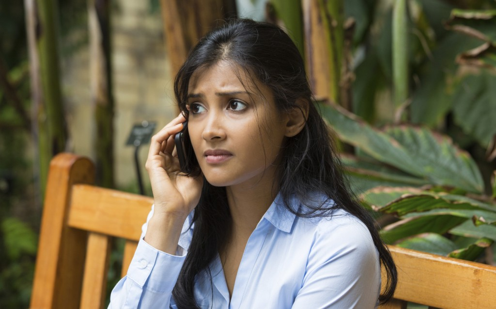 Closeup portrait, sad, depressed, unhappy worried young woman talking on phone, sitting on bench, isolated trees background.