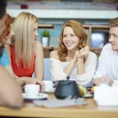 Young woman sitting at café among her friends