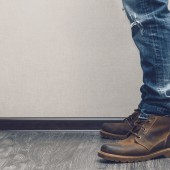 Young man's legs in jeans and boots on wooden floor