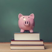 Piggy bank on top of books with chalkboard creating a cost of education theme