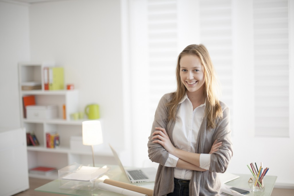 young woman arms crossed standing in front of desk