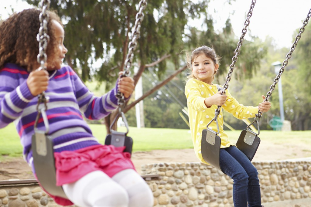 Two Young Girls Playing On Swing In Playground