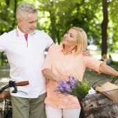 Mature couple spending time together at park with bicycles