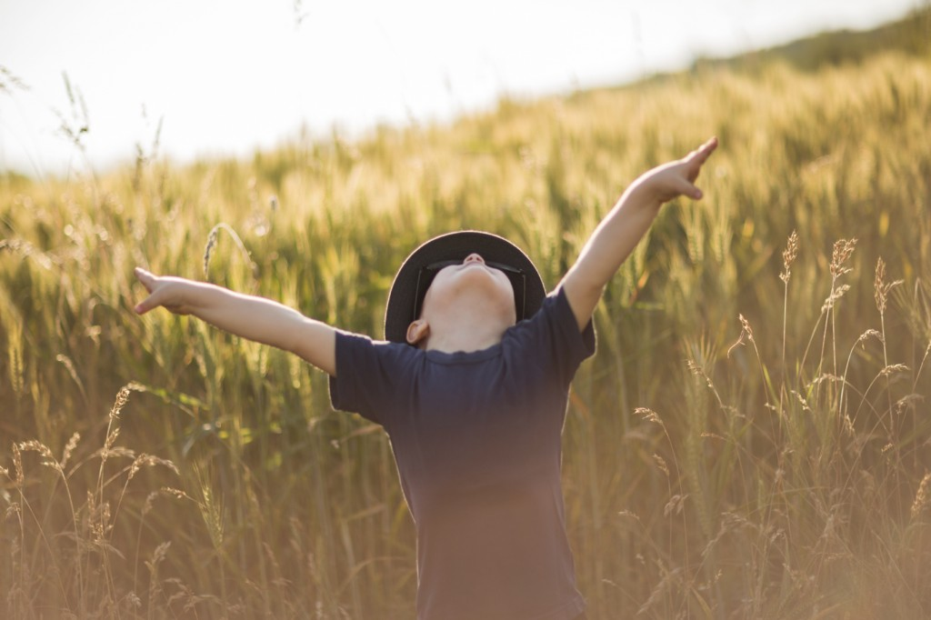 little boy with arms raised in a sunset field