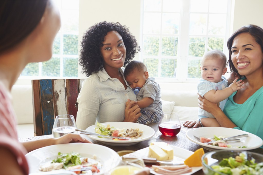 Female Friends With Babies Enjoying Meal At Home Together