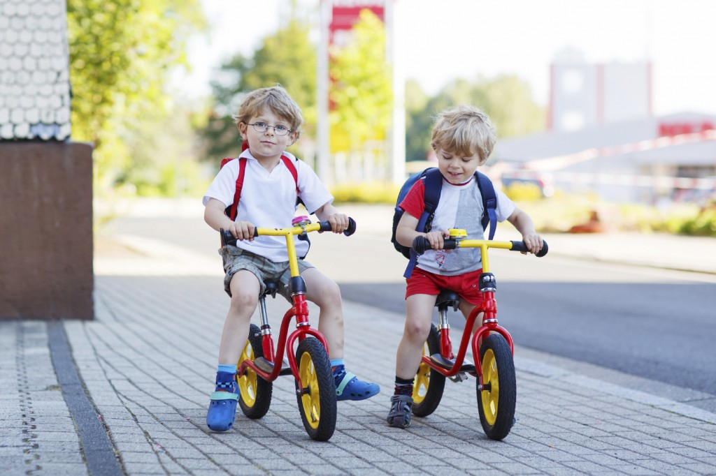 Two little siblings children having fun on bikes in city, outdoo