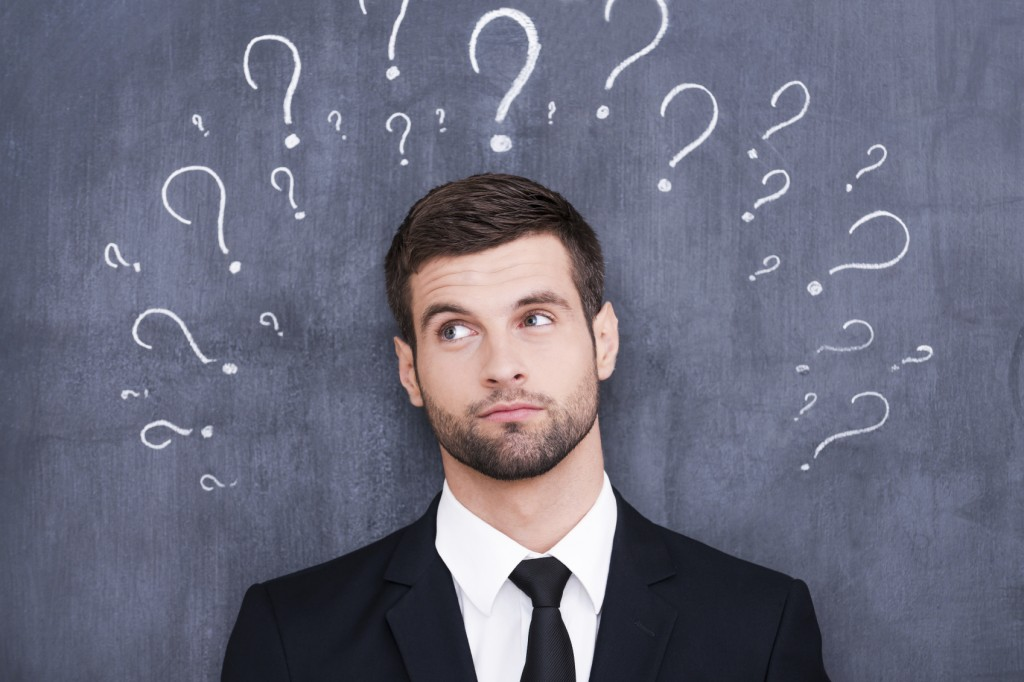 Confused young man standing against blackboard with question marks