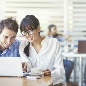 Man and woman using laptop and laughing