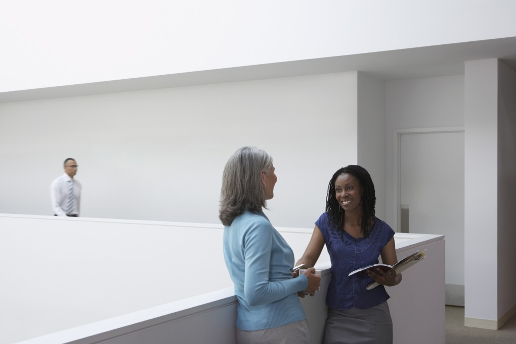 women Talking In Office Hallway
