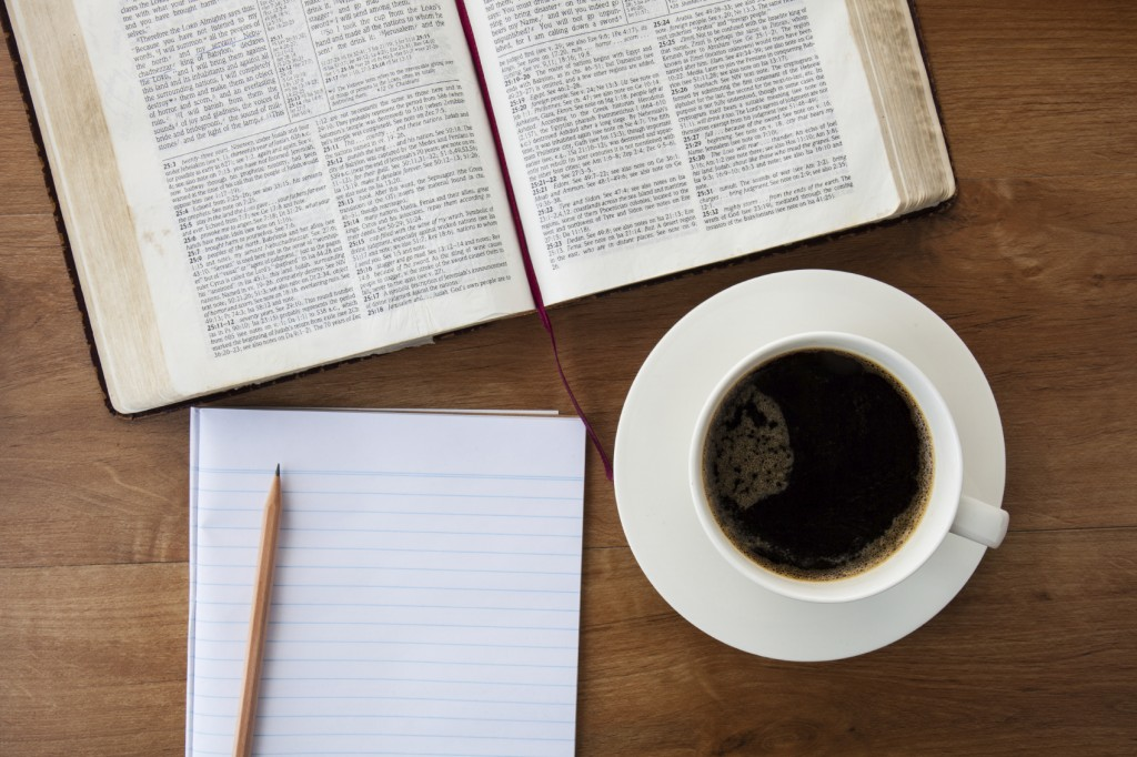 Reading the Bible with morning cup of coffee on wood table in the office.
