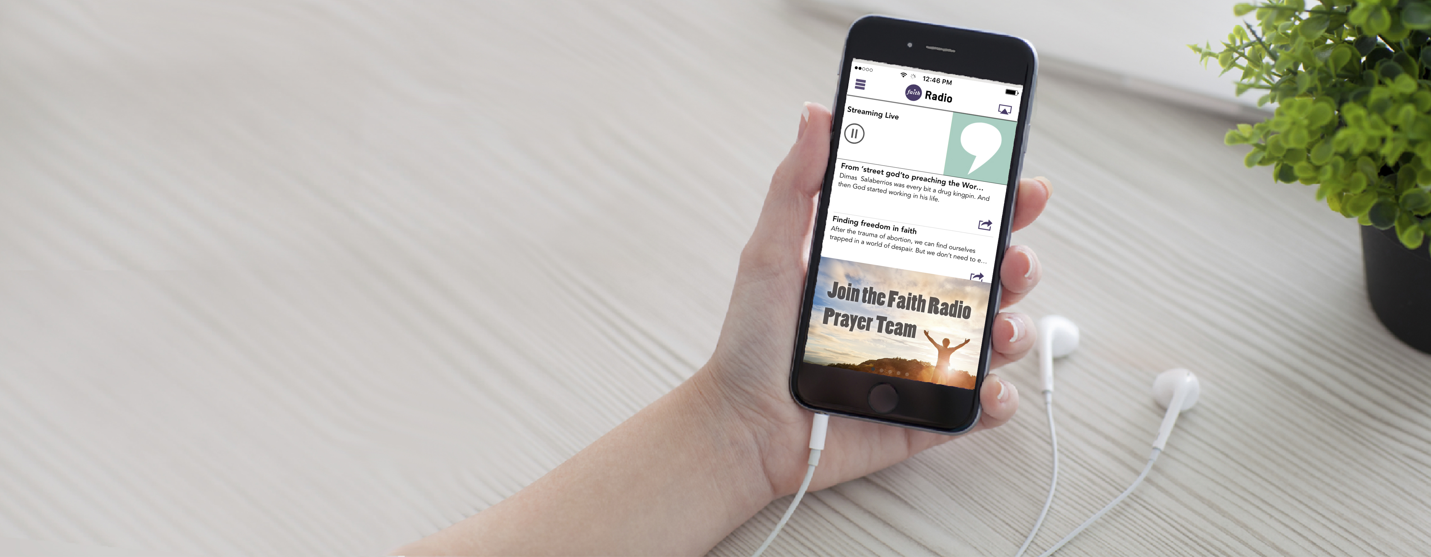 Woman holding iPhone 6 with the Faith Radio App on the screen