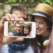 Young couple taking selfie with smart phone camera in outdoors.