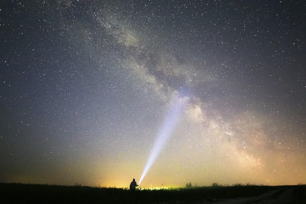 man shining flashlight at star lite sky