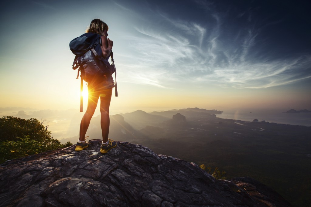 Lady hiker relaxing on top of hill and enjoying sunrise over the valley