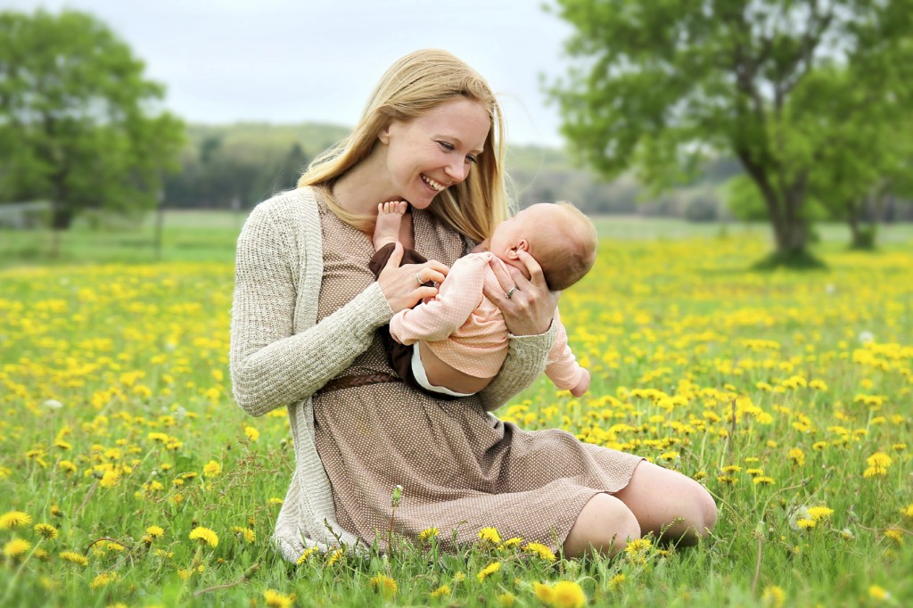 Happy Young Mother Playing with Newborn Baby Outside