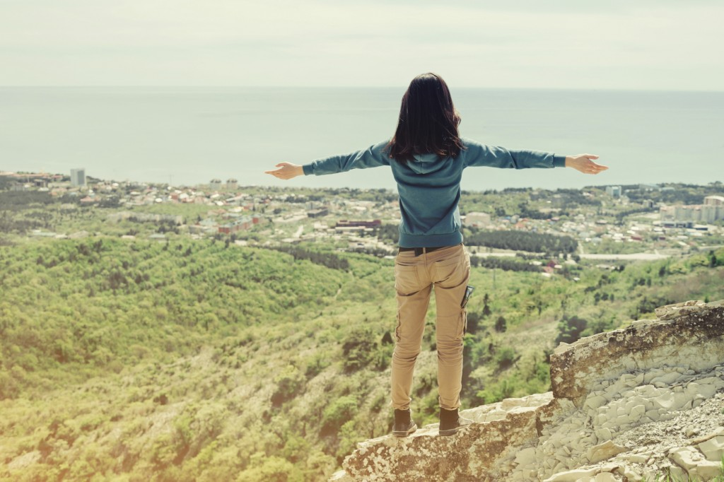 Traveler woman standing with raised arms on peak of rock