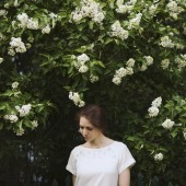 Woman standing next to a bush of white lilac
