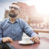man sitting in a cafe at market square in sunset.