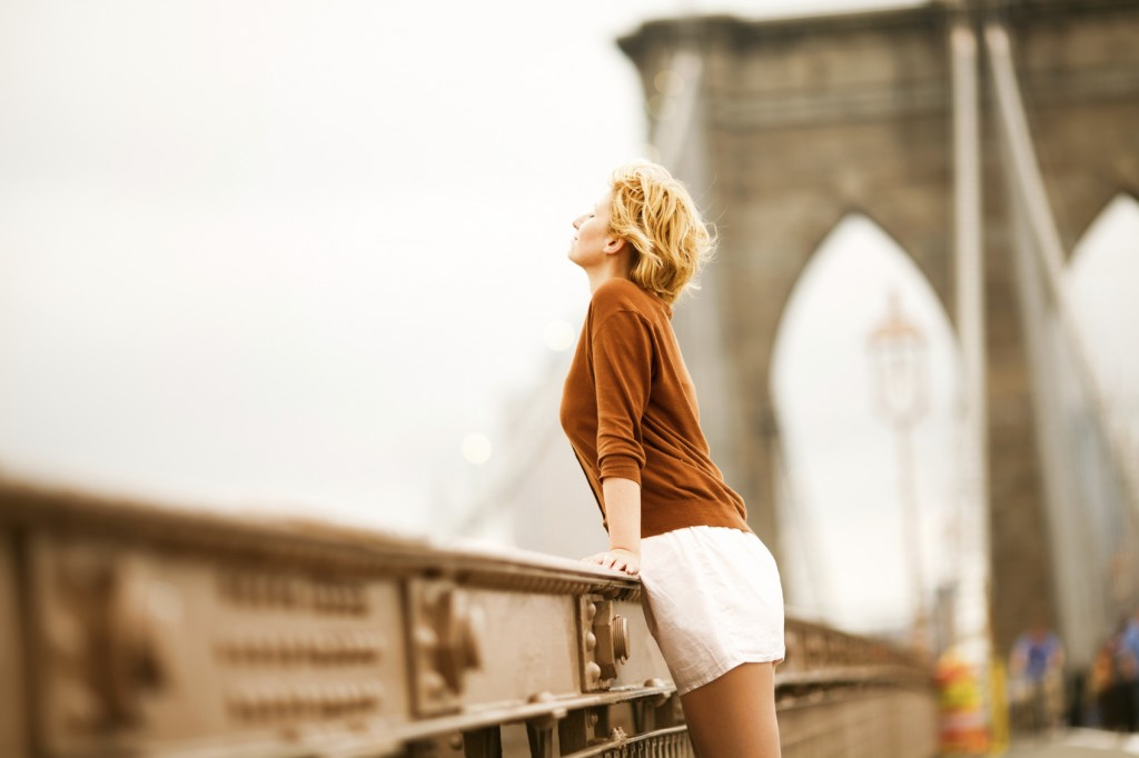woman looking over a bridge breathing deep