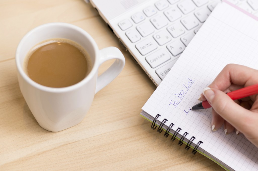 To do list. Woman writing a 'to do list' at her desk with a cup of fresh coffee