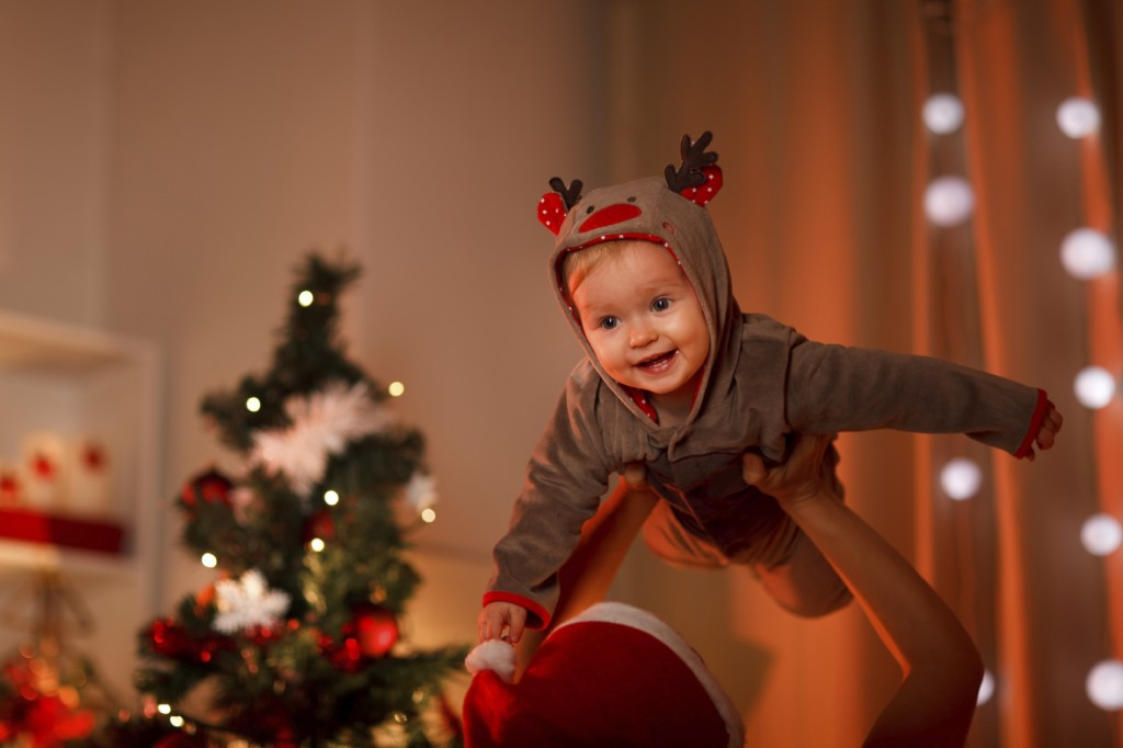 Adorable baby having fun near Christmas tree