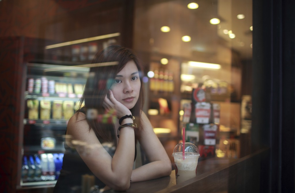 Young girl looking out behind the cafe window