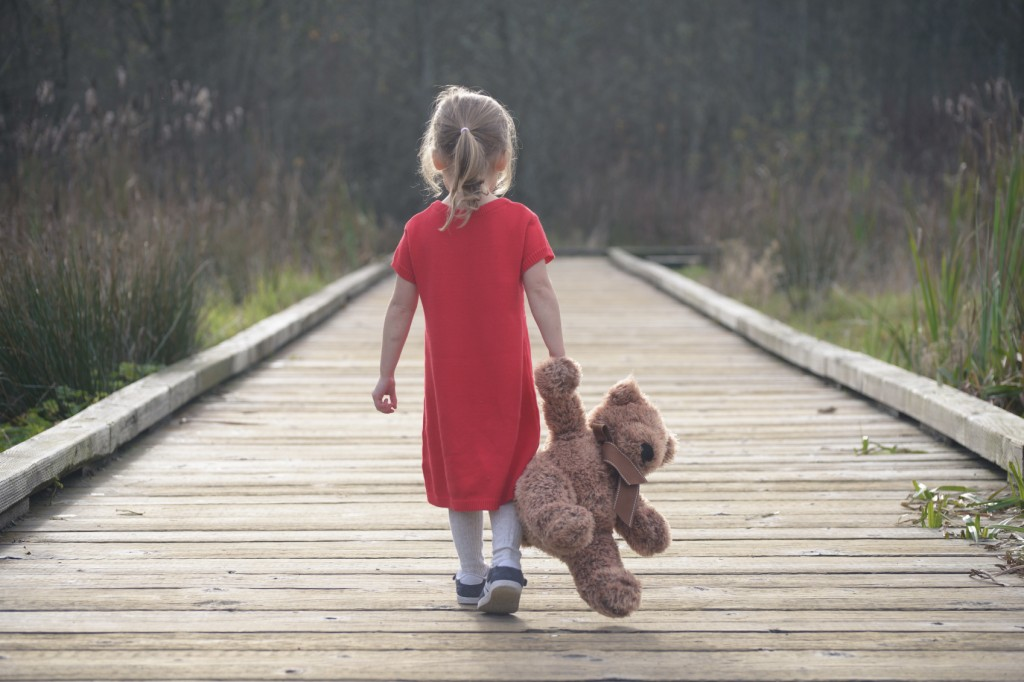 Little girl in a red dress walking on boardwalk away holding teddy bear, view from behind