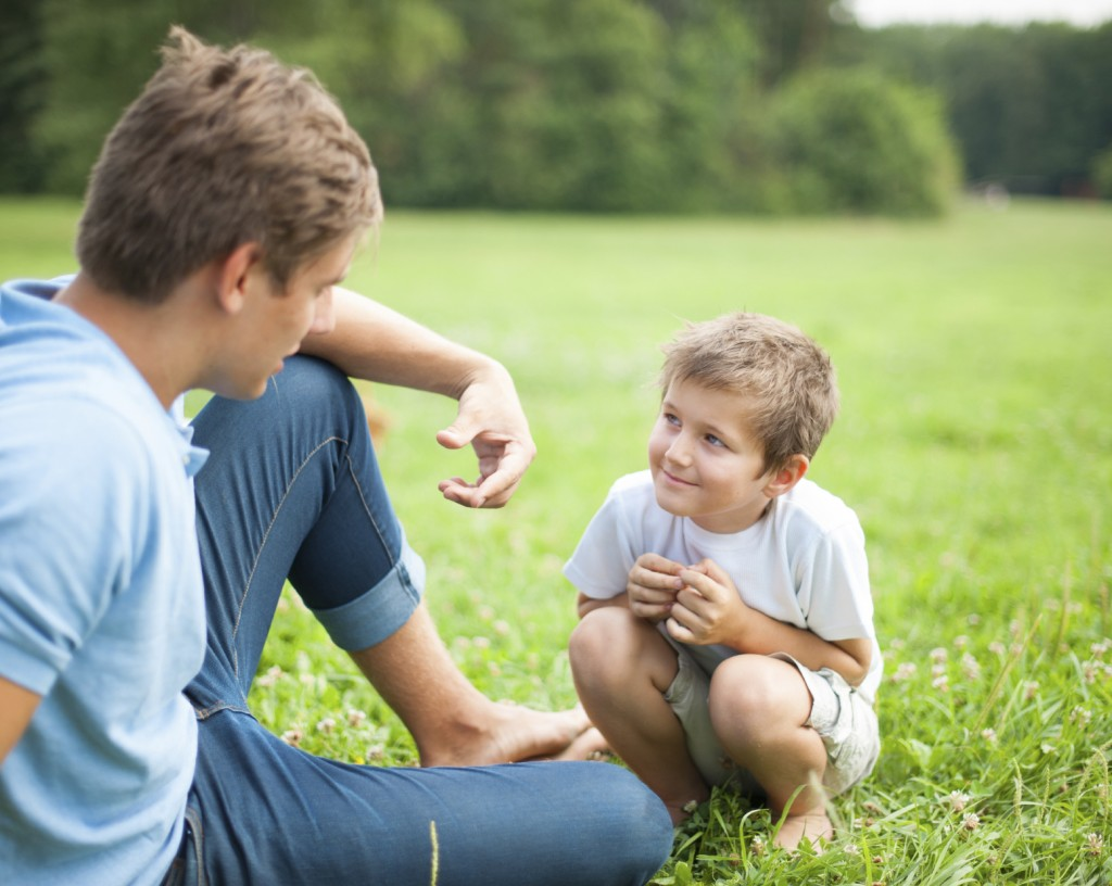 Father and son talking in park