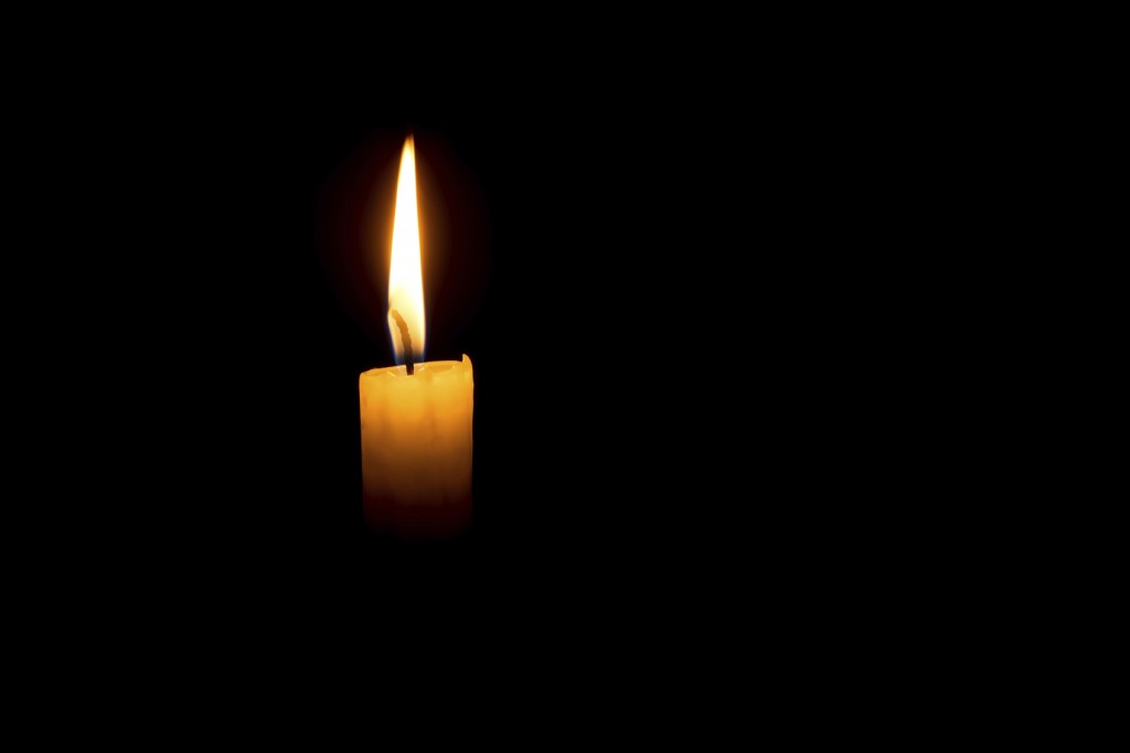 single candle in a dark room. concept of grief
