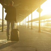 Man standing with bag and mobile phone at train station
