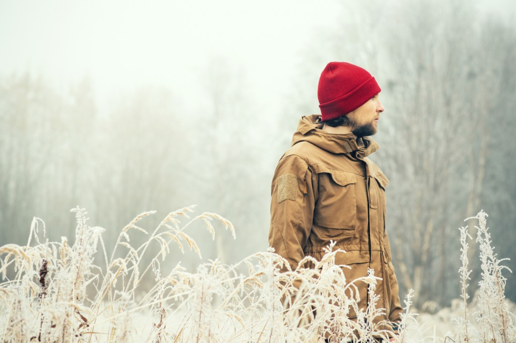 Young Man wearing winter hat clothing outdoor with foggy forest nature