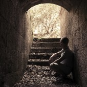 Young man sits inside of dark stone tunnel