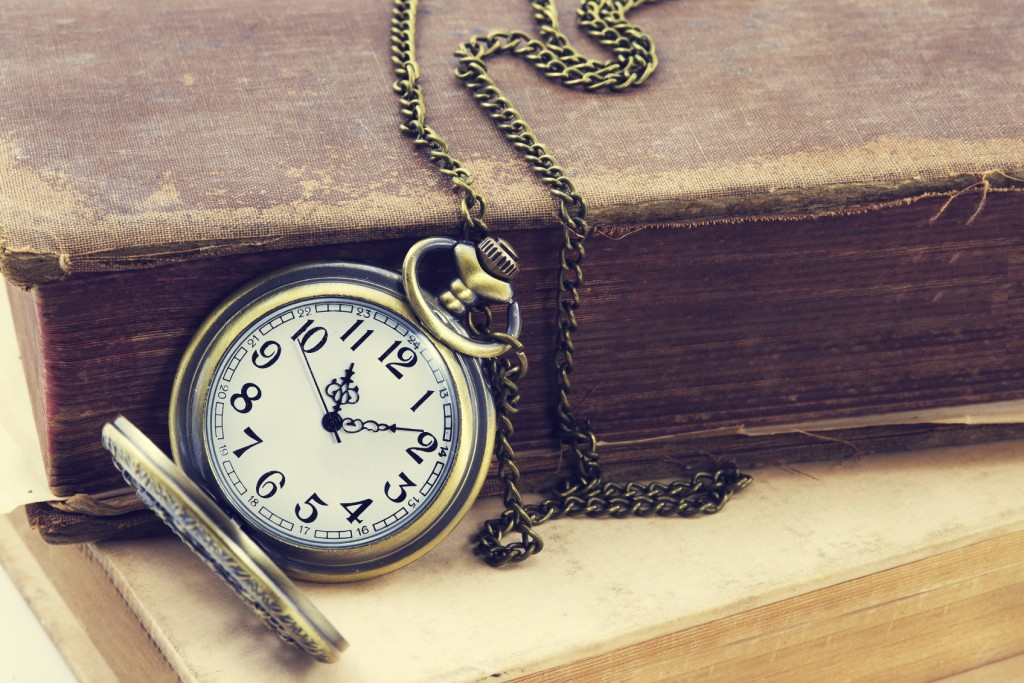 Vintage grunge still life with antique pocket watch, and old book