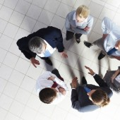 Above angle of several smart associates talking to each other at meeting