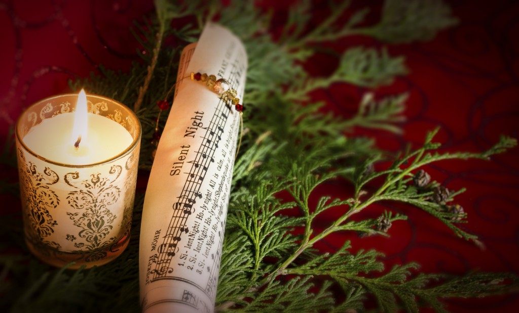 Christmas Carol music with candle and pine