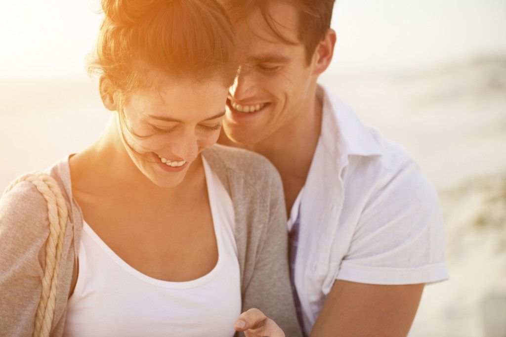 young couple sharing intimate moment smiling on beach