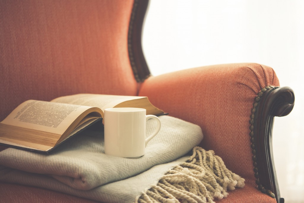 Book, cup and warm plaid on cozy retro armchair.