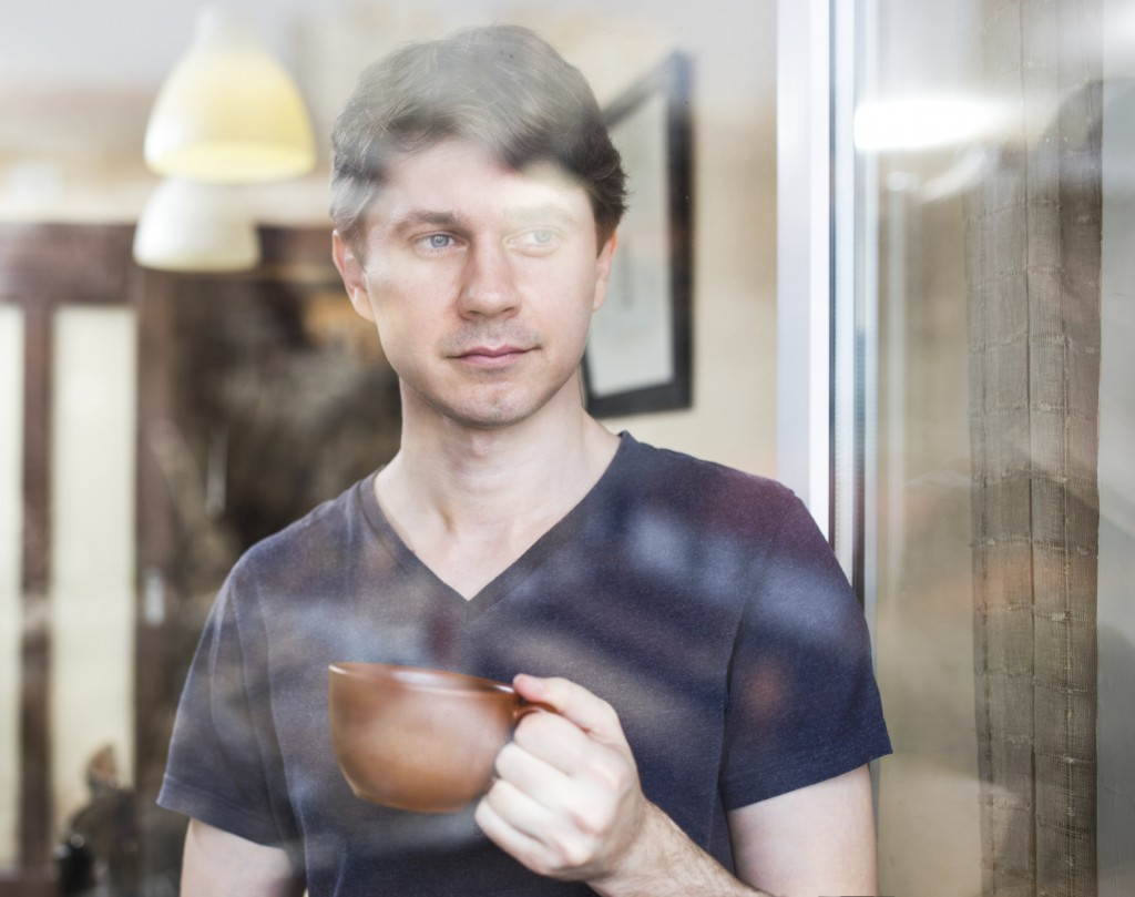 Man at home, drinking coffee or tea near window