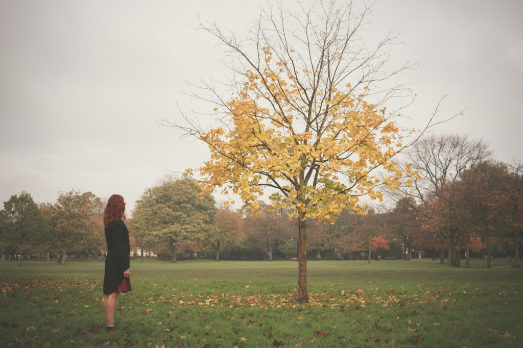 Woman standing by tree in autumn